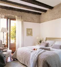 Dormitorio con parte de la pared de ladrillos a la vista y vigas