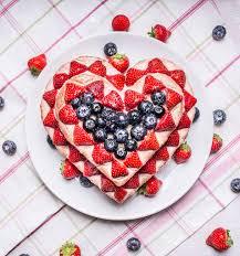 selbst gemachter kuchen mit erdbeeren und heidelbeeren zum valentinstag herz auf einem weißen teller auf einem gestreiften tischdecke förmig mit rund
