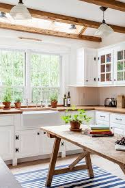 A Farm Style Kitchen With Clean White Lines And Contrasting Raw Timber