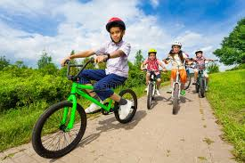 Download African Guy Rides Bike With Friends Riding Behind Stock Photo