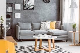 hölzerner couchtisch auf schwarzweiss teppich im wohnzimmer mit gelbem kissen auf grauem sofa