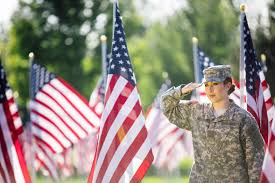 American Female Soldier Saluting In Front Of Flags