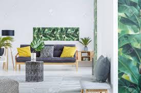 hocker im hellen wohnzimmer mit gelben kissen auf sofa gegen weiße wand mit grünem plakat