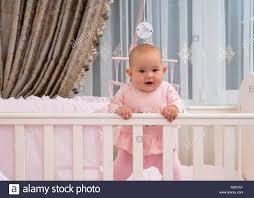 ein glückliches lachendes baby mädchen in einer krippe in