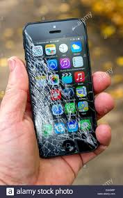 Smartphone iPhone 5 with broken display screen held by a hand