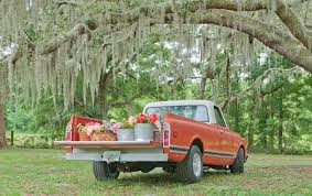 Red Ford Truck With Flower Buckets On Bed