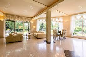 helles marmor gestaltetes wohnzimmer fenstern umgeben mit zwei großen sofas essbereich mit stühlen