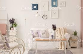 echtes foto weißen wohnzimmer interieur mit frischem lavendel poster an wand kaffeetisch mit kerzen und sofa mit kissen stockfoto und mehr bilder