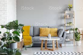 orange kissen und decke auf graue im wohnzimmer interieur mit holztisch echtes foto stockfoto und mehr bilder decke bettwäsche