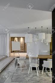 zimmer in einem modernen stil mit weißen wänden und einem parkett mit grauen fliesen mit mustern auf dem boden es gibt einen holztisch mit weißen
