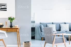 weiß und grau öffnen raum wohnzimmer interieur mit gemusterten sessel schreibtisch aus holz mit rosa tulpen und mit zwei kissen stockfoto und
