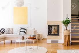 kupferner couchtisch auf weißem teppich im wohnzimmer mit kamin und goldmalerei an der wand