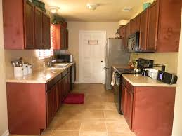 Simple Galley Kitchen Design Showing Brown Cabinets And Steel Fridge Near The Door