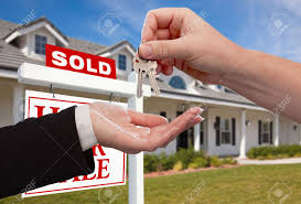 Handing Over The House Keys In Front Of Sold New Home Against A Blue Sky Stock