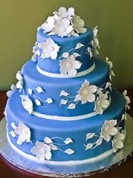 Round three tier bright blue fondant wedding cake decorated with beautifully made white sugar paste