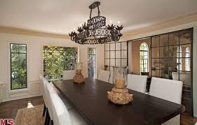 The Dining Room Features An Elegant Table And Chairs Set Lighted By A Grand Chandelier