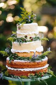 A Semi Naked Three Tiered Wedding Cake Adorned With Wildflower Like Blooms