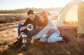 Happy Young Couple Making Coffee Outdoors Near A Tent In The Morning