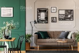schwarz weiß fotos auf graue wand schicke wohnund esszimmerinterieur mit braunen sofa und tisch aus holz stockfoto und mehr bilder aufgeräumter