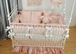 pink floral and silk crib bedding with white bows on a white bratt