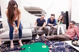 gruppe junge erwachsene haben spaß spielen golf im wohnzimmer