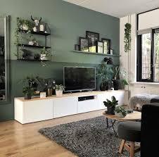 wohnzimmer mit weißem tv schrank und grüner wand gruner