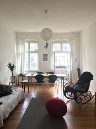 wohn esszimmer mit großen fenstern in berliner altbau