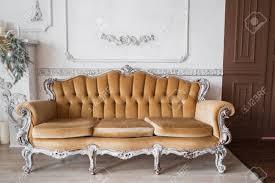 wohnzimmer mit antiken stilvollen beige sofa auf luxus weißen wand design basrelief stuck formteile rokoko elemente schwarz weiß foto