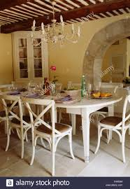 Simple Cream Metal Chandelier Above Painted Chairs And Table In French Country Dining Room