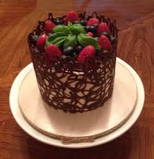 A dark chocolate cage surrounds cake topped with strawberries blueberries and basil