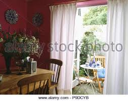 Pine Table And Chairs In Pink Diningroom With White Curtains At French Doors View Of