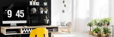 hölzerner schreibtisch und tischrechner die in einem arbeitsplatz mit wohnzimmer im hintergrund stehen