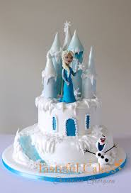 A two tiered Frozen Castle Cake with a handmade sugar model of Elsa and the Snowman