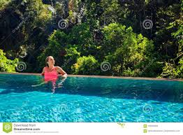 100 Infinity Swimming Woman Relaxing In Luxury Spa Hotel In Pool Stock