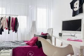 arbeitszimmer und schlafzimmer kombiniert innenraum mit weißem stuhl schreibtisch und großem bett mit bunter bettwäsche