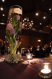Pink floating tulips in glass cylinder with glass beads and floating