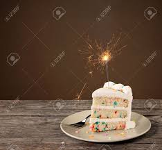 Slice of Birthday Cake with colorful sprinkles and lit sparkler Stock