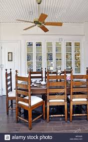 Ceiling Fan Above Wooden Table And Chairs In Traditional Style Dining Room