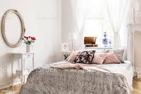 englisch style schlafzimmer innenraum mit bett mit leichten grauen bettwäsche und rosa limonade und muster kissen und weiße verzierte möbel und