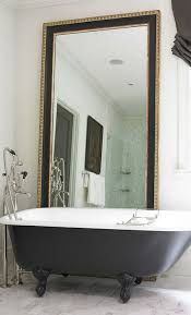 sophisticated bathroom features a black and gold floor mirror