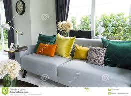 modernes wohnzimmer mit grauem sofa und bunten kissen