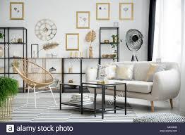 gold stuhl neben schwarz und beige sofa im wohnzimmer