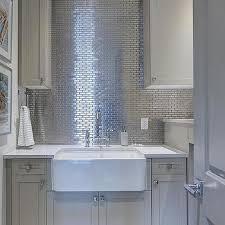 ivory laundry room with stainless steel mini tile backsplash