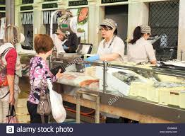 two ladies shopping at fresh fish market inside mercato albinelli