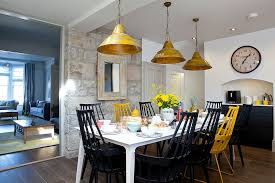 Beach Style Dining Room With Accent Stone Wall And Colorful Chairs Design Camellia Interiors