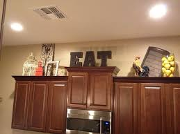 how to decorate the space above your kitchen cabinets how to