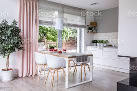 graue römische farbtöne und ein rosa vorhang auf große glasfenster in eine moderne küche und esszimmer interieur mit einem holztisch und weiße stühle