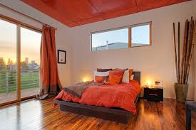 Minimalist Medium Tone Wood Floor And Orange Bedroom Photo In Seattle With Beige Walls