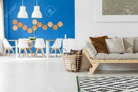 kissen im korb im geräumigen wohnzimmer mit speisetische gegen blaue wand und graues sofa gegen weiße wand