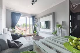 helles geräumiges wohnzimmer mit einem bequemen grauen sofa einem weißen tisch einem großen fernseher und einem balkon
